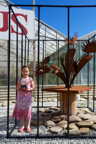 Proudly holding her plant next to the sculpture out front